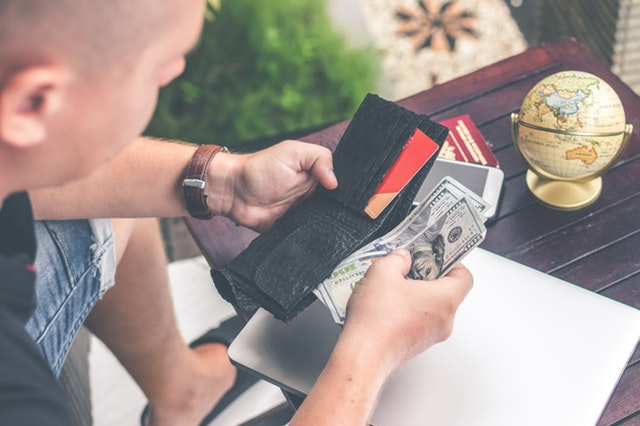 person checking his cash in wallet